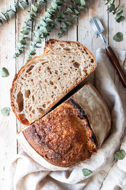 From above homemade fresh sourdough bread in tablecloth on wooden table — Stock Photo