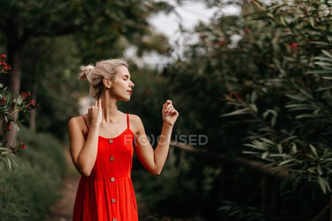 Vista laterale di attraente bionda vestita di rosso sensualmente posa e tocca il collo con gli occhi chiusi tra alberi verdi in fiore — Foto stock