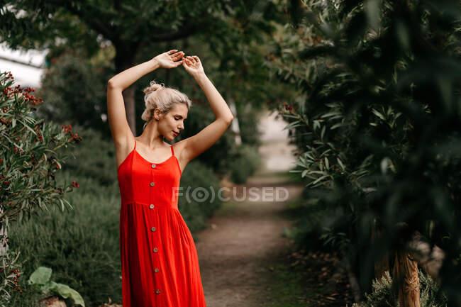 Боковой вид привлекательной блондинки, одетой в красное чувственное позирование с закрытыми глазами среди зеленых цветущих деревьев — стоковое фото