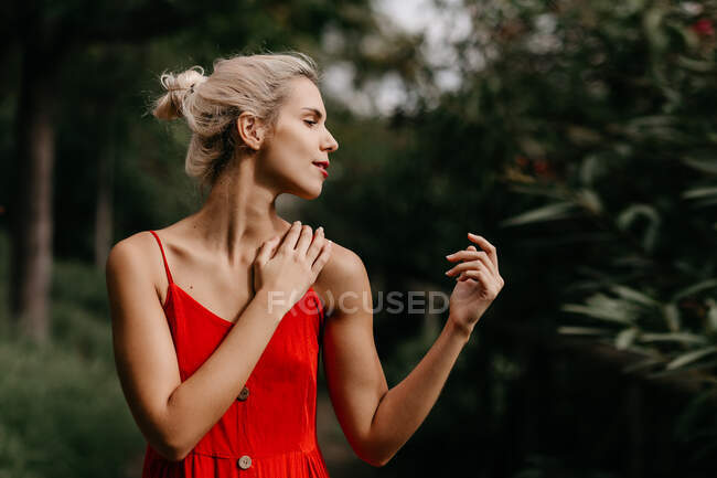 Side view of attractive blonde dressed in red sensually posing and touching her neck with closed eyes among green blooming trees — Stock Photo
