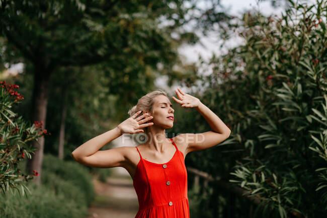 Бічний вид на привабливу блондинку, одягнену в червоне чуттєве полотно з закритими очима серед зелених квітучих дерев. — стокове фото
