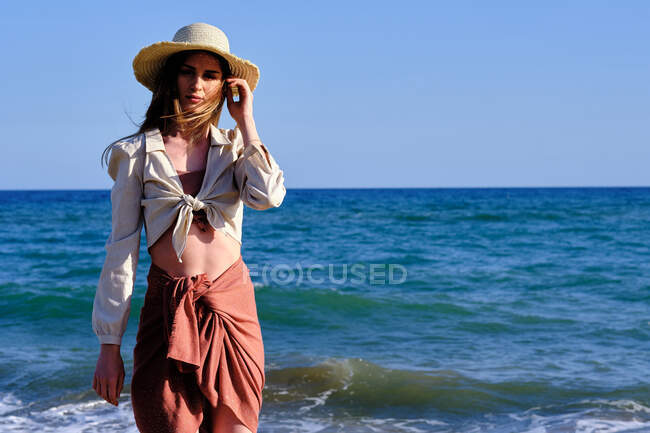 A fashion model with a hat at the beach before sunset — Stock Photo