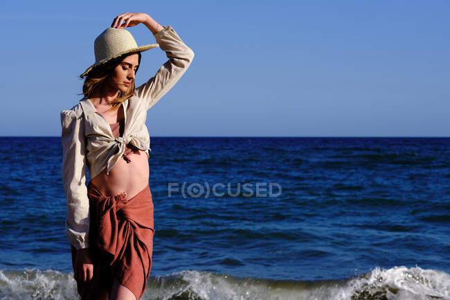 Una modelo de moda con sombrero en la playa antes del atardecer - foto de stock