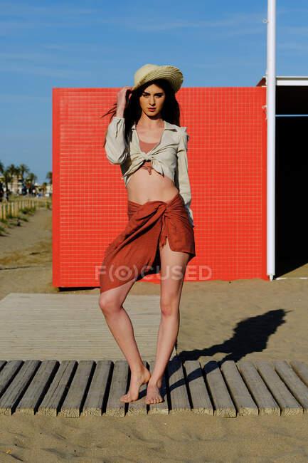 Una modelo de moda de pelo largo con sombrero en la playa frente a una pared roja - foto de stock