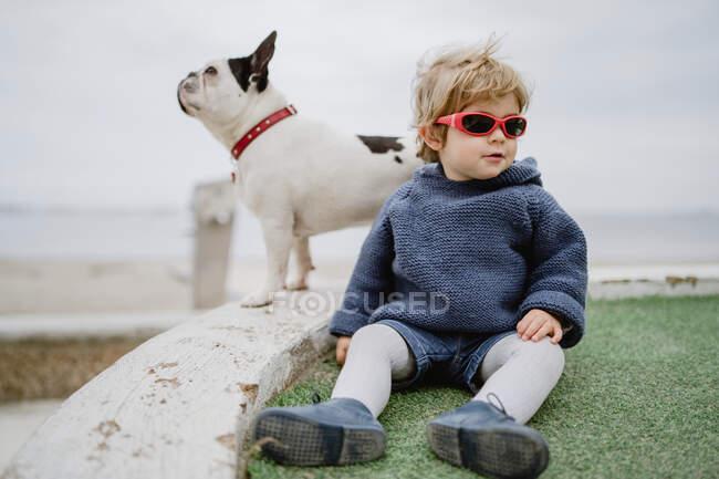Приваблива дитина посміхається і бавиться з сонцезахисними окулярами, сидячи на пляжі біля пляжу французького бульдога — стокове фото
