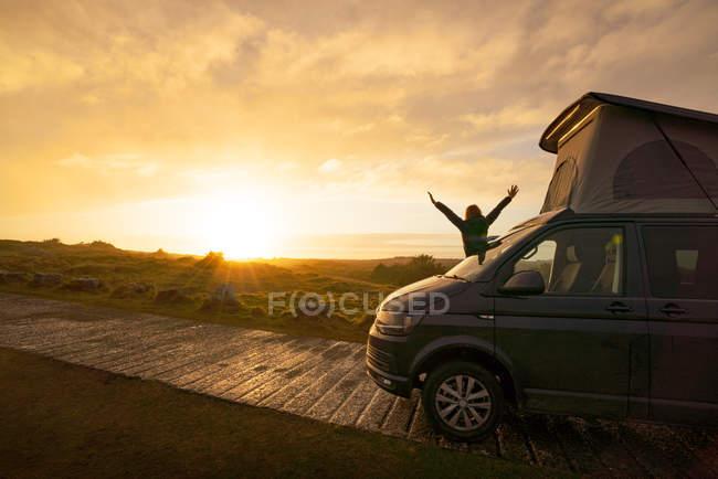 Silhouette féminine avec les mains ouvertes debout sur caravane remorque sur route de campagne solitaire au coucher du soleil au Pays de Galles — Photo de stock