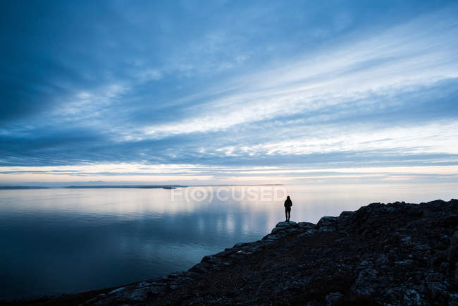 Silhouette of woman standing on rocky coastline at sunset in Wales — Stock Photo