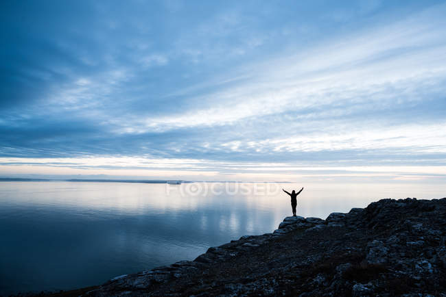 Happy silhouette féminine sur la côte rocheuse au coucher du soleil au Pays de Galles — Photo de stock