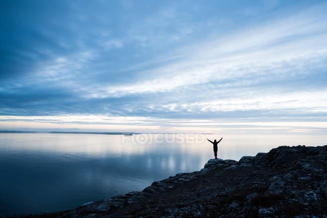 Silhueta feminina feliz no litoral rochoso ao pôr do sol no País de Gales — Fotografia de Stock