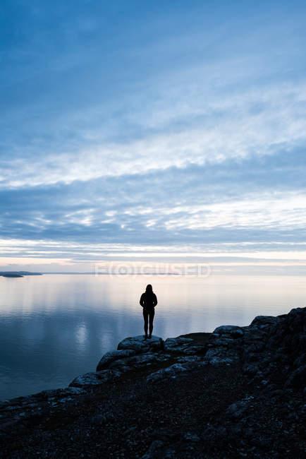 Silhouette di donna in piedi sulla costa rocciosa al tramonto in Galles — Foto stock