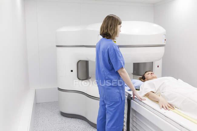 Mujer de mediana edad y su médico en una máquina de resonancia magnética abierta esperando a que comience la prueba - foto de stock