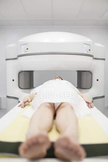 Mujer de mediana edad en una máquina de resonancia magnética abierta esperando a que comience la prueba - foto de stock