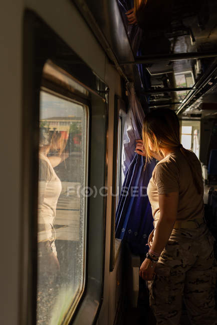 Soldat féminin regardant par la fenêtre tout en voyageant par la campagne dans le véhicule militaire — Photo de stock