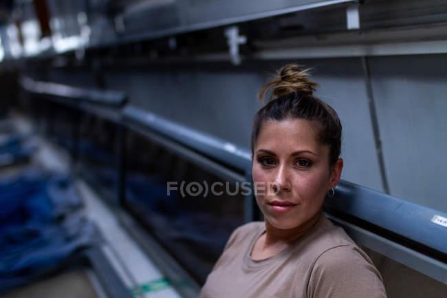 Atractiva soldado femenina mirando a la cámara dentro del moderno transporte militar - foto de stock