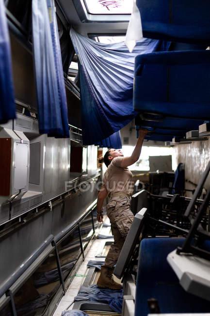Atractiva soldado mujer mirando hacia arriba mientras está de pie dentro del transporte militar moderno - foto de stock