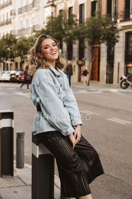 Attractive happy woman in trendy outfit sitting on bollard on city street — Stock Photo