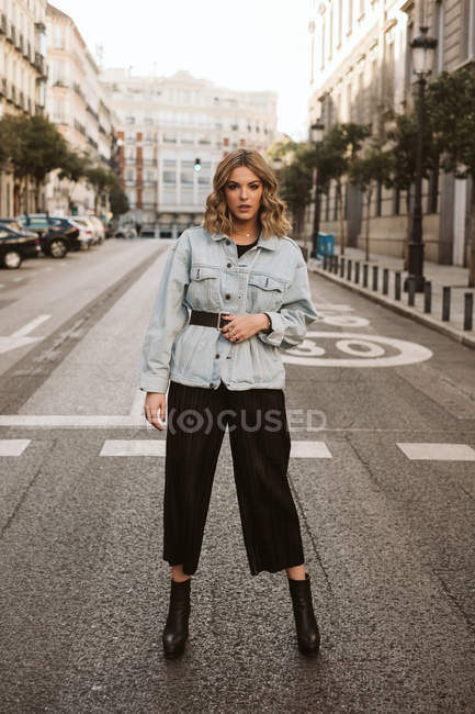Stylish female in trendy outfit standing in middle of asphalt road on city street — Stock Photo