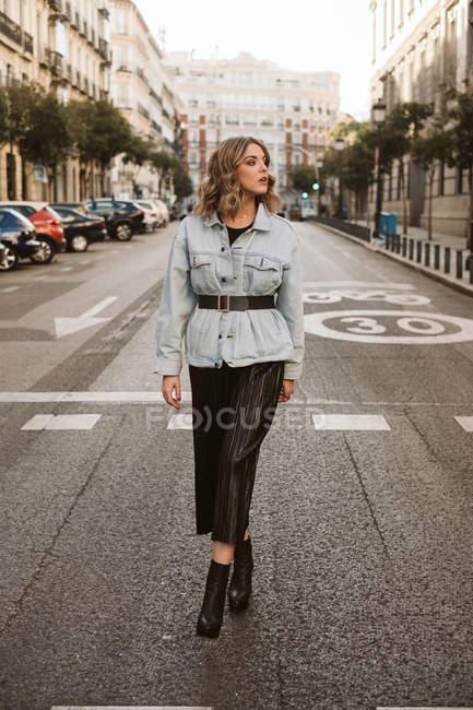 Attraente donna in abito alla moda in piedi in mezzo alla strada asfaltata sulla strada della città — Foto stock