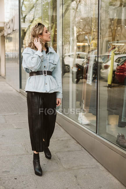 Attractive young female in stylish outfit looking at clothes behind shop window while walking on city street — Stock Photo