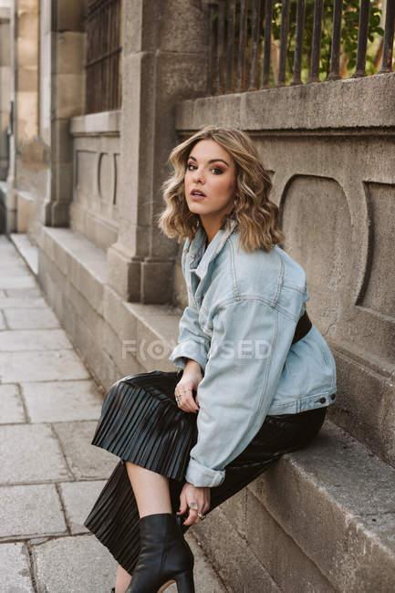 Молодая леди в стильном наряде, смотрящая в камеру, сидя возле каменного забора городского парка — стоковое фото
