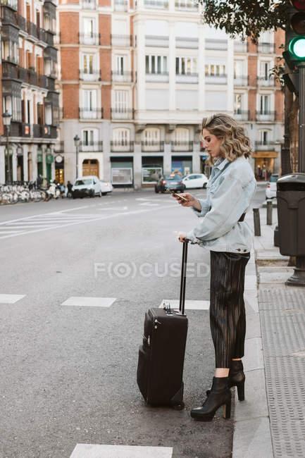 Стильная молодая женщина с помощью мобильного телефона с чемоданом при пересечении улицы города — стоковое фото