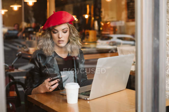 Trendy young female in red beret using mobile phone while sitting at table with laptop in restaurant — Stock Photo