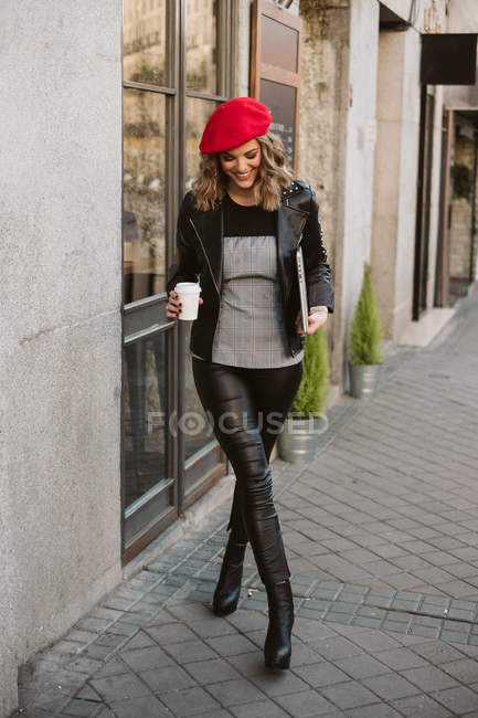 Stylish happy young female in red beret holding takeaway beverage while walking out coffee shop on city street — Stock Photo