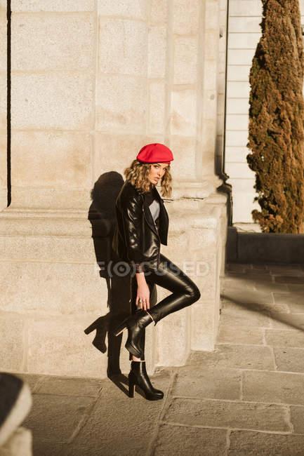 Стильная молодая женщина в модном красном берете и смотрит в камеру, стоя на городской улице в солнечный день — стоковое фото