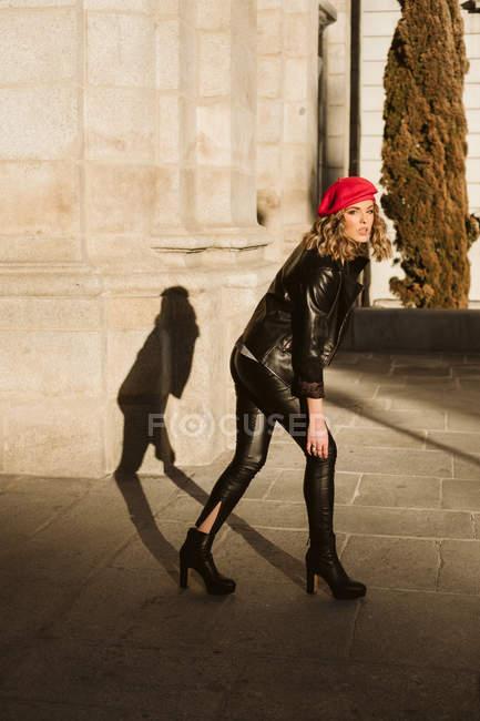 Стильна молода жінка носить модний червоний бере і дивиться на камеру, стоячи на міській вулиці в сонячний день — стокове фото