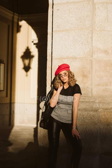 Чуттєва молода жінка в модних бере і окуляри тримає шкіряну куртку на плечі і дивлячись на камеру, стоячи біля будівлі стіни на сонячний день на вулиці міста — стокове фото