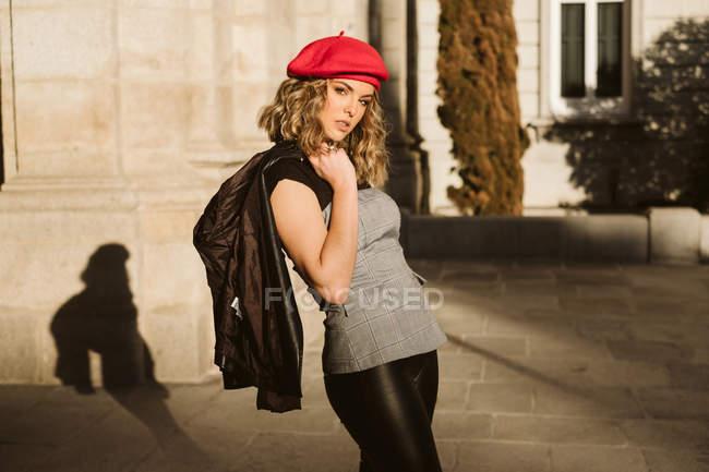 Чувственная молодая женщина в модном берете держит кожаную куртку на плече и смотрит в камеру, стоя возле стены здания в солнечный день на городской улице — стоковое фото