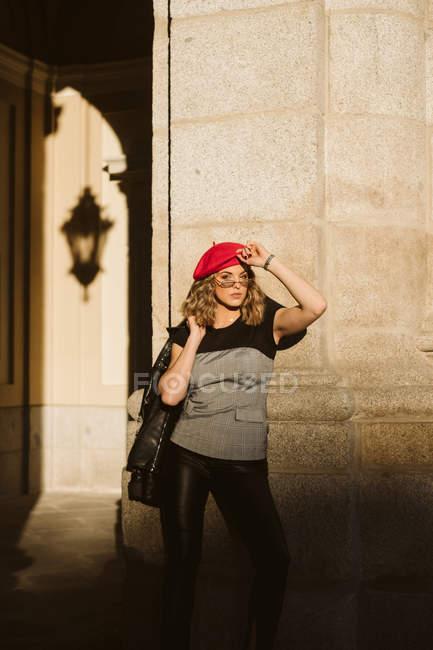Чувственная молодая женщина в модном берете и очках держит кожаную куртку на плече и смотрит в камеру, стоя возле стены здания в солнечный день на городской улице — стоковое фото