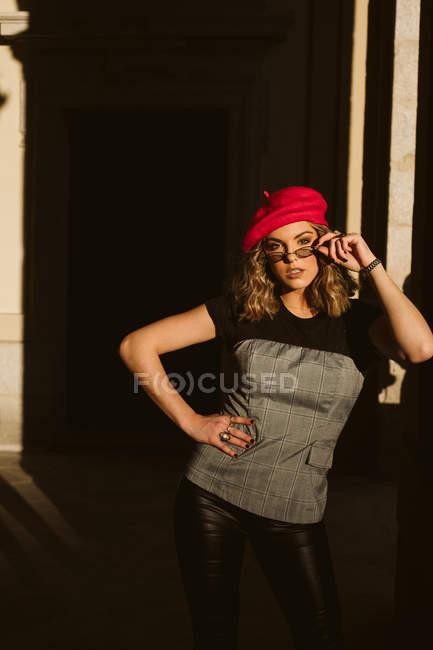 Jovem sensual na boina da moda e óculos olhando para a câmera enquanto estava perto da parede do edifício no dia ensolarado na rua da cidade — Fotografia de Stock