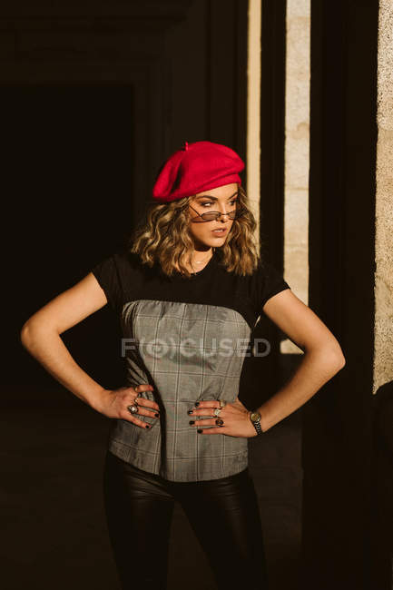 Confident young woman in trendy beret and glasses standing near building wall on sunny day on city street — Stock Photo