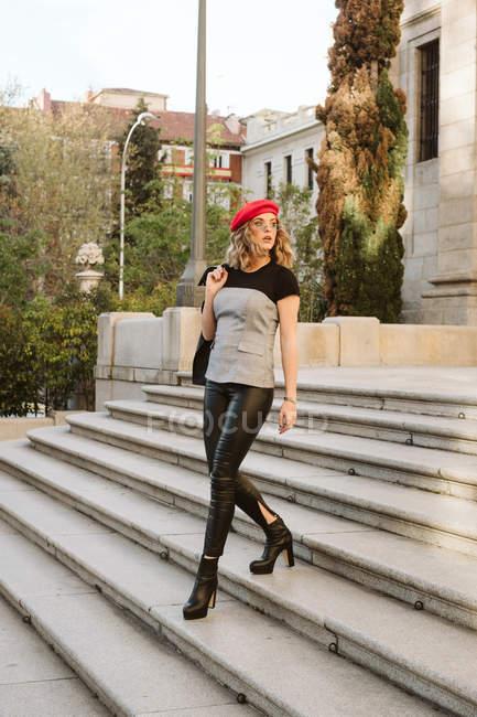 Молодая женщина в стильном красном берете смотрит вниз по улице — стоковое фото