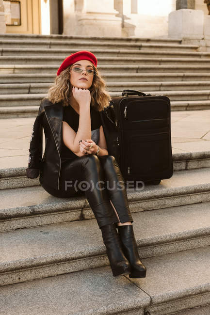 Thoughtful young woman in trendy outfit with modern sunglasses sitting on stairs near suitcase — Stock Photo