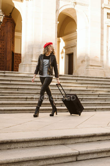 Young woman in trendy outfit with modern sunglasses walking on stairs with suitcase — Stock Photo