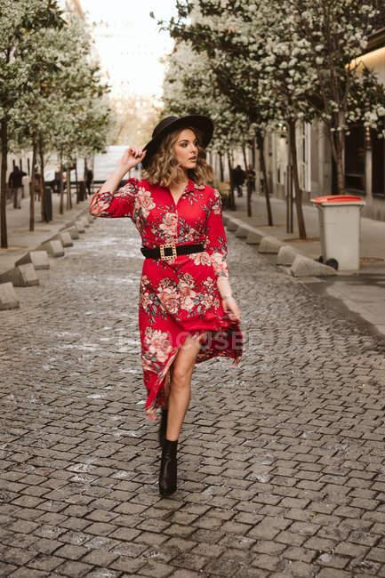 Jeune femme en robe élégante et chapeau regardant loin tout en marchant sur le trottoir âgé sur la rue de la ville — Photo de stock