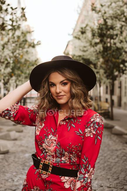 Giovane donna in abito elegante e cappello guardando la fotocamera mentre sul marciapiede invecchiato sulla strada della città — Foto stock