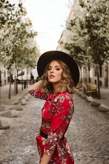 Чуттєва молода жінка в стильному одязі і капелюсі дивлячись на камеру, стоячи на витримані тротуар на міській вулиці — стокове фото