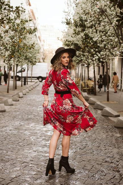 Vista posterior de la mujer joven en vestido elegante y sombrero mirando a la cámara sobre el hombro mientras camina sobre el pavimento envejecido en la calle de la ciudad - foto de stock