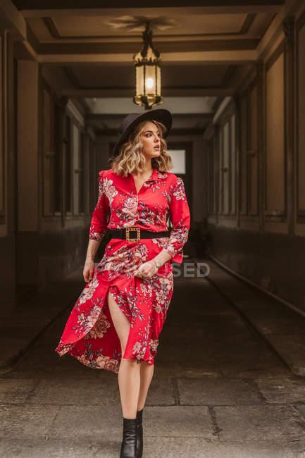 Jeune femme élégante en robe élégante et chapeau regardant loin tout en marchant sous la lampe dans le passage de vieux bâtiment — Photo de stock