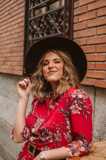 Allegra giovane donna in abito elegante e cappello guardando la fotocamera vicino vecchio edificio sulla strada della città — Foto stock