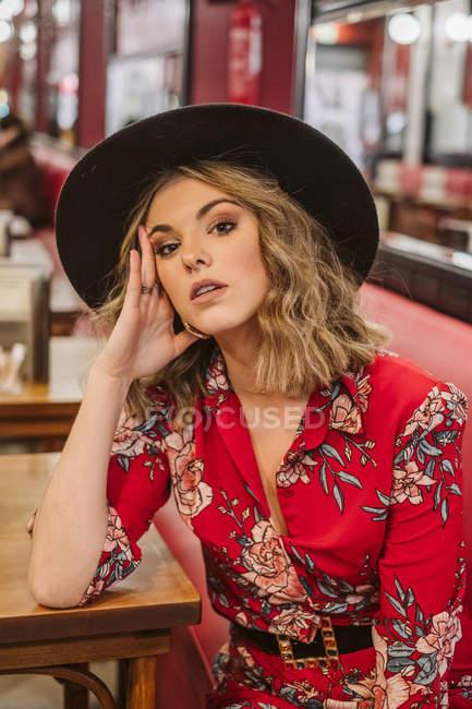 Sensuale giovane donna in elegante abito elegante e cappello seduto sul divano rosso vicino al tavolo e guardando la fotocamera nel ristorante — Foto stock