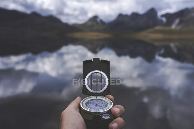 Hand of anonymous traveler holding compass against tranquil mountain lake on cloudy day in Spanish countryside — Stock Photo