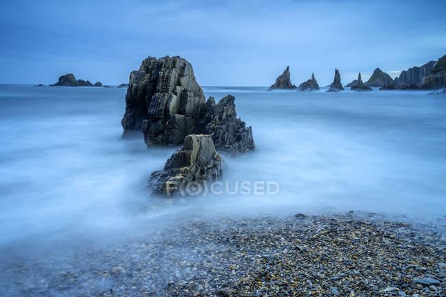 Seascape of Playa de Gueirua seashore with stones on misty day at Asturias, Spain — Stock Photo