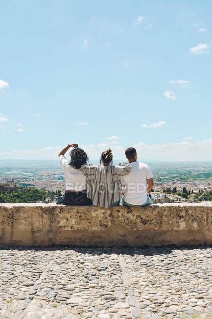 Група друзів займається туризмом в Іспанії і роздумує над панорамними поглядами Альгамбри в Гранаді. — стокове фото
