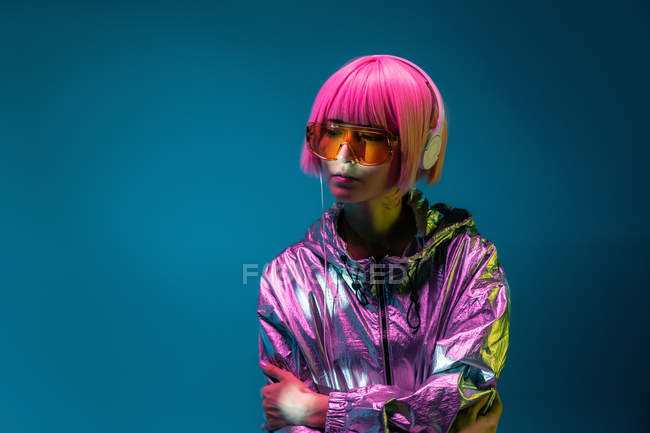 Young Asian woman with stylish pink haircut and sparkly silver jacket standing and listening music — Stock Photo
