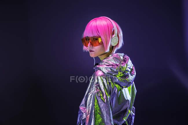 Молодая азиатка со стильной розовой стрижкой и блестящей серебряной курткой стоя и слушая музыку — стоковое фото