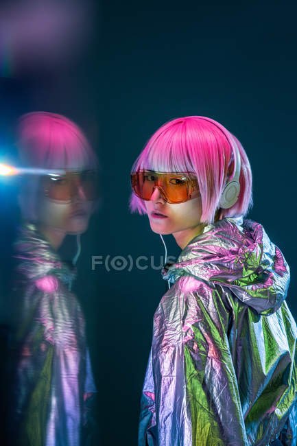 Fashionable attractive young Asian woman with pink hair in silver jacket listening music on dark background with reflection — Stock Photo